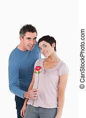 Man offering a rose to his wife against a white background