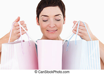 Woman looking at her shopping bags against a white...
