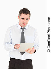 Portrait of a businessman using a tablet computer against a...