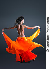 Beauty girl with naked spine dance in orange cloth
