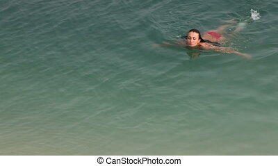 Swimmer - Young woman swimming in water and then getting out...