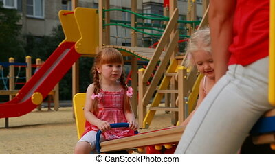 Mother with girls - Mother and two little girls on swings