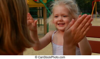 Clapping hands - Little girl playing with palms on...