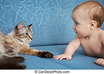 Baby and cat - Baby and the cat lay on the couch and stare...