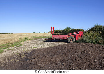 red manure spreader - an agricultural landscape with a red...