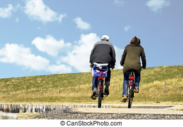 A couple cycling on a causeway in Zeeland - A young couple...
