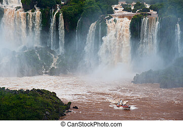 Iguazzu Falls, South America - A boat full of tourists enjoy...