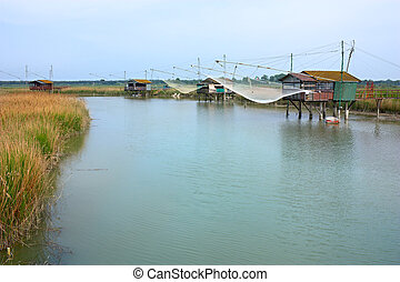 fishing shacks - fishing huts - shacks with net on the river...
