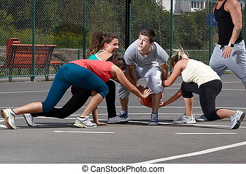 Leisure time in a park - Young people playing basketball in...