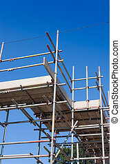 Scaffolding erected for building new houses. Blue sky above...