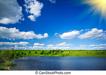 Lake, meadow and blue sky by springtime.