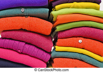 Stack of women's sweaters and cardigans in bright vivid colours against white.