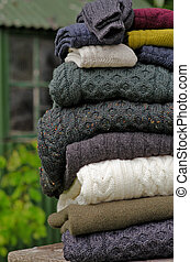 Stack of chunky Irish wool cable knit and Aran winter sweaters plus socks in fall and winter colours in a pretty Irish rural setting.