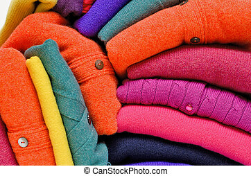 Stack of women's sweaters and cardigans in bright vivid...