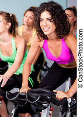 Group of four people spinning in fitness club - Group of...