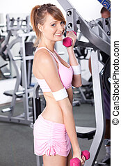 Beautiful sporty woman with a dumbbell