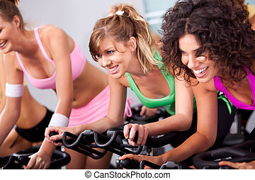 Females cycling in spinning class in gym - Gorgeous young...
