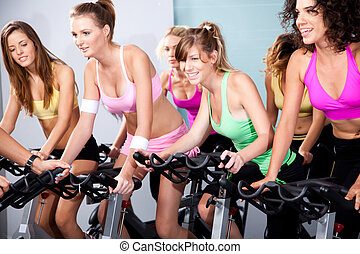 Attractive females on bicycles in a fitness club - Four...