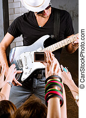 Guitarist playing for is fans - Rock guitarist playing in...