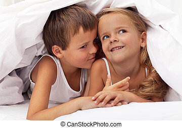 Kids planning the next prank hidden under the quilt
