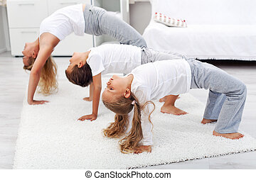 Woman and kids doing gymnastic exercises at home - Woman and...