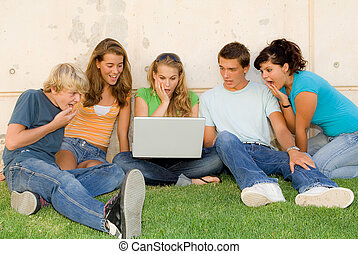 surprised group of teenagers with laptop or notebok