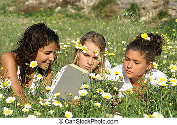 group of healthy happy girls reading in flower field