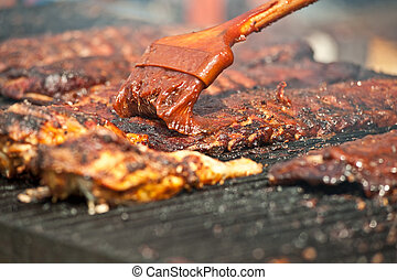 Basting tasty ribs on the barbeque