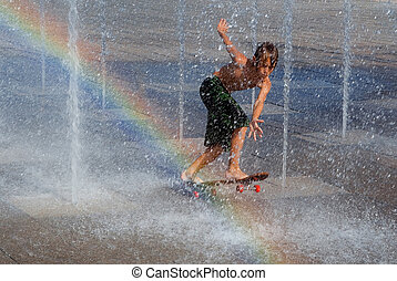 kid cooling off playing on skateboard in fountain