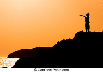 child with arms raised in joy at the vacation sunset