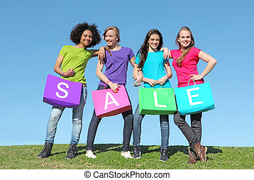 group of girls shopping in sales with bags - group of happy...