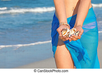 woman on beach on summer vacation collecting shells