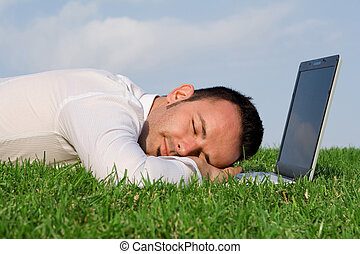 business man relaxing having power nap outdoors with computer laptop