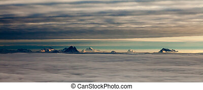 Distant snowcapped mountain peaks between two layers of...