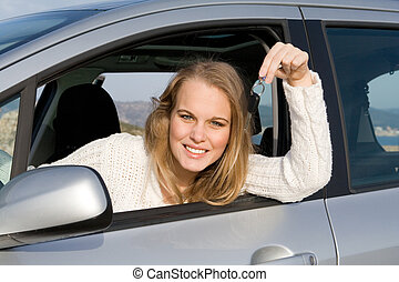 young woman holding key to new, hire or rental car after passing, driving test