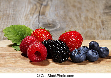 wild berries on a chopping board on wooden background
