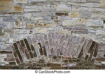 background or texture of a stone wall with brick insertion
