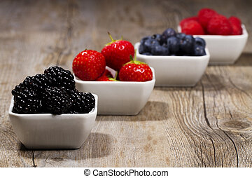 some bowls filled with wild berries on wooden background...
