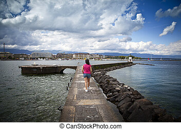 Young woman walking in the Jet d'Eau dock in Geneva