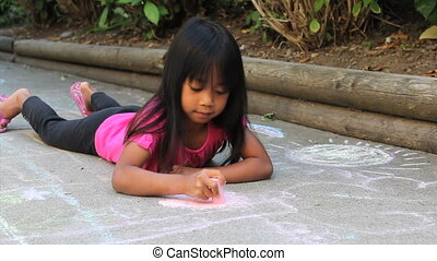Asian Girl Doing Sidewalk Chalk - A cute little Asian girl...