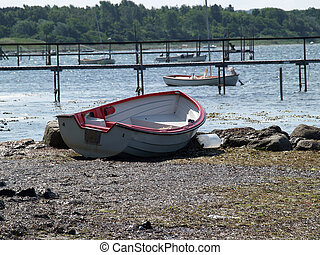 Small fishing boat dory rowboat on the shore - Small...