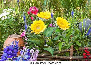 Rural pot on a wattled fence with a sunflower and wild...
