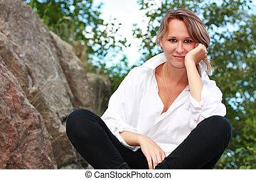 A beautiful young woman sitting cross-legged among the...