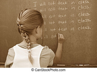 old school - Little girl writing lines on a chalkboard in...