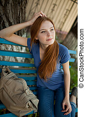 sad girl sitting on a park bench - girl sitting on a bench