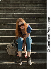 beautiful red-haired girl sitting on the stairs with a bag -...