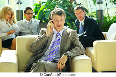 business man speaking on the cell phone while in a meeting