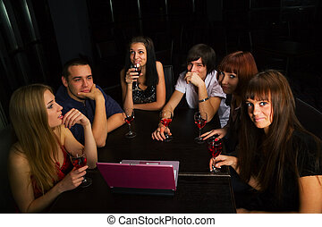 Young friends with laptop in a bar - Young friends drinking...