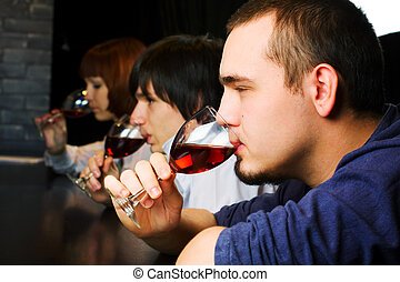 Young people relaxing in a bar - Young people drinking red...