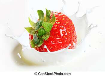 Strawberry falling into milk with splashes